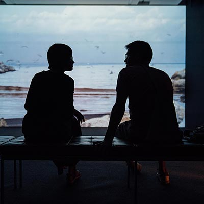 silhouettes of two people having a conversation on a bench