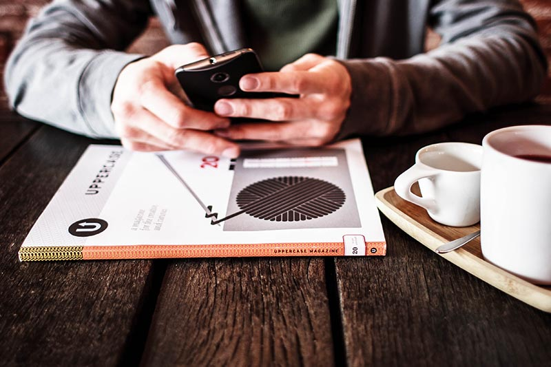 man texts on phone at table with book and coffee