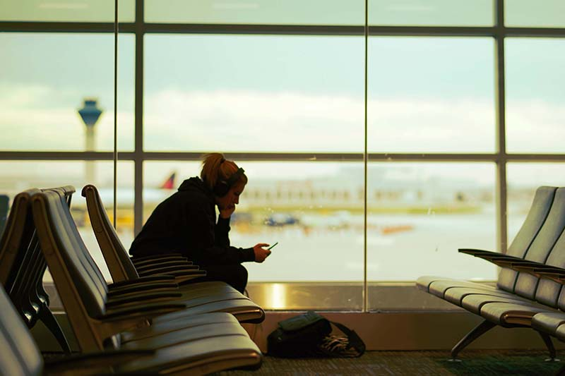 woman with headphones sits in airport waiting area