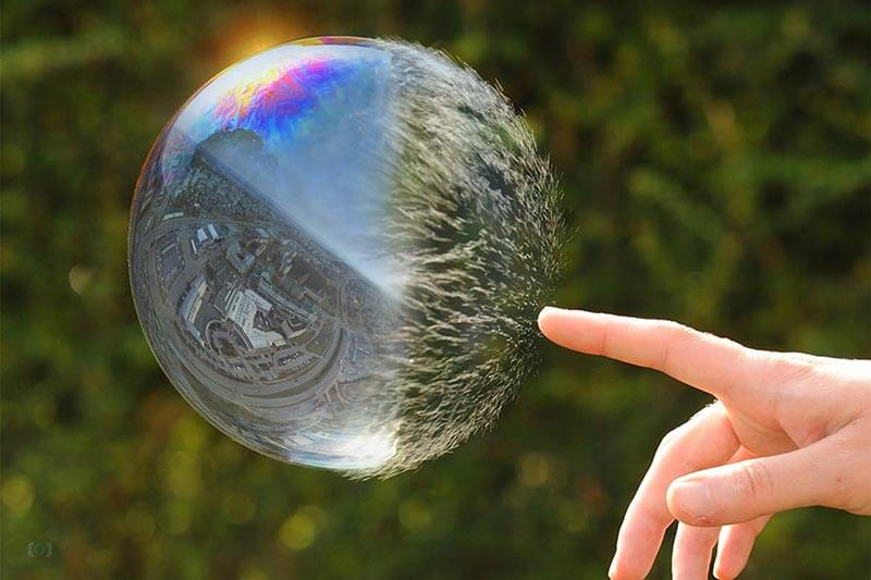 hand popping bubble outside