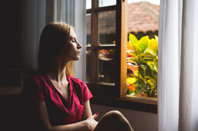 woman managing anxiety looking out window