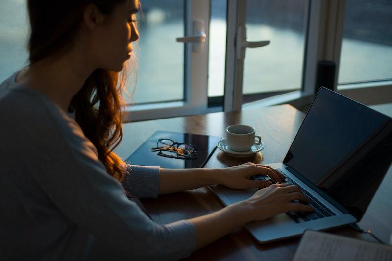 woman working on laptop by open window